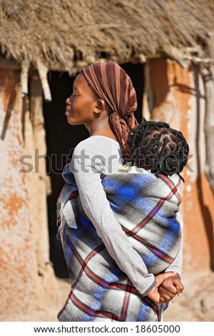African mother carry child in a traditional way in front of the hut - stock photo