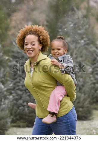 African mother giving daughter piggy back ride - stock photo