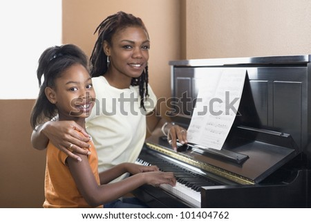African mother helping daughter with piano lessons - stock photo
