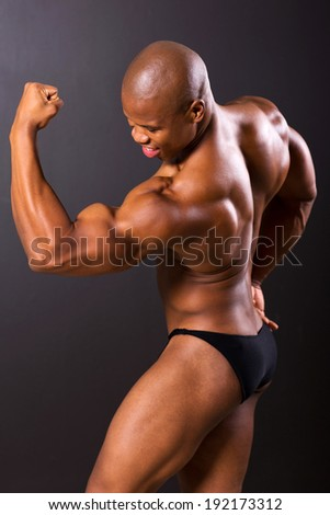 african muscular man showing muscles on black background - stock photo