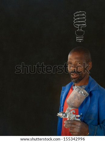 African or American black man industrial worker with chalk energy saving lightbulb on blackboard background - stock photo
