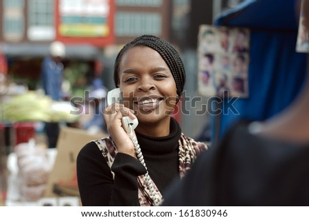 African or black American woman calling on landline telephone in Alexandra township - stock photo