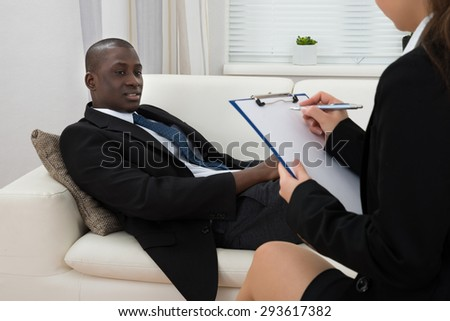African Patient Sitting On Couch And Female Psychiatrist Writing On Clipboard - stock photo