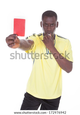 African Referee Holding A Red Card With Whistle In His Mouth - stock photo