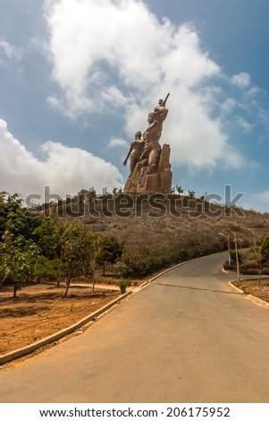 African Renaissance Monument, a 49 meter tall bronze statue of a man, woman and child, in Dakar, Senegal - stock photo