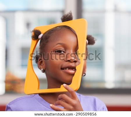 African schoolgirl joking with object in primary classroom. - stock photo