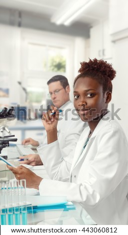 African scientist, medical or or graduate student. Bright, confident young woman wearing lab coat holds a pen and a notebook. A senior Caucasian male colleague on a background. This image is toned. - stock photo