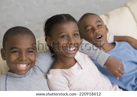 African siblings laughing on sofa - stock photo