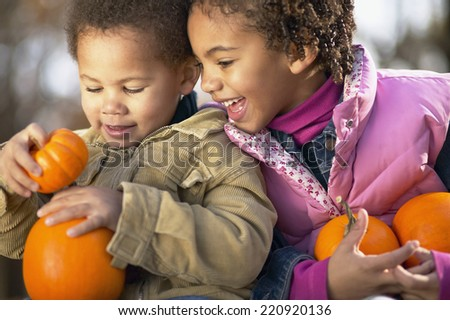 African sister and brother holding pumpkins - stock photo