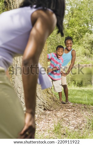 African sister and brother playing with mother in park - stock photo