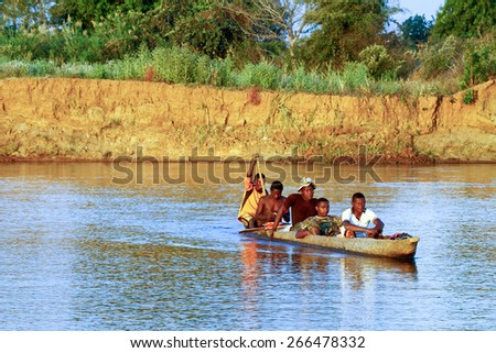 African soldier during operation - transported by traditional canoe, Madagascar - stock photo