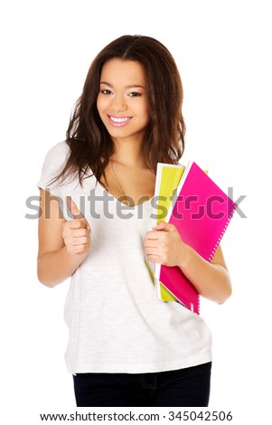 African student woman with notes and thumbs up.