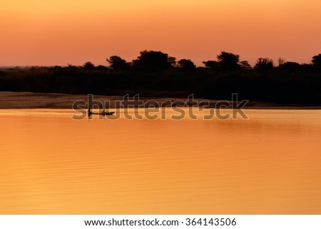 African sunset on Zambezi river with two peoples in small traditional boat, Caprivi strip region, Namibia - stock photo