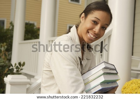 African woman carrying stack of books - stock photo