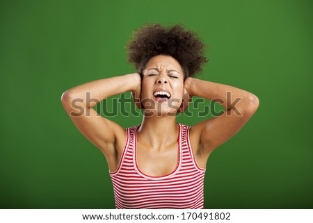 African woman covering ears with her hands, over a green background - stock photo