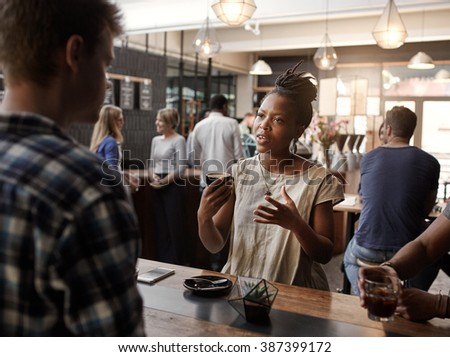 African woman describing something at a coffee shop business mee - stock photo