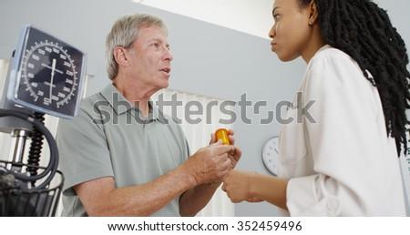 African woman doctor prescribing medicine to patient - stock photo