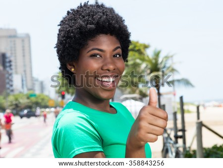 African woman in a green shirt in the city showing thumb - stock photo