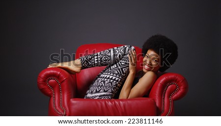 African woman in red leather arm chair kicking legs playfully - stock photo
