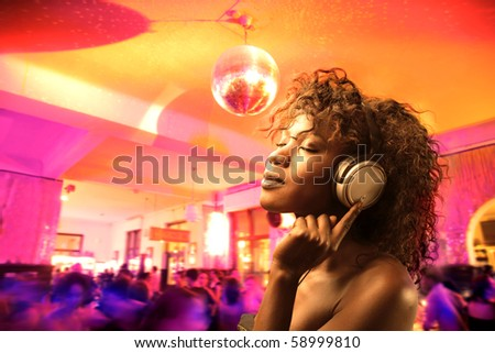 African woman listening to music with disco on the background