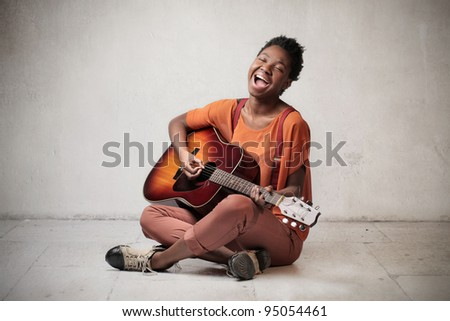 African woman playing the guitar and singing out loud - stock photo
