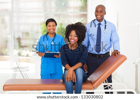 african woman sitting on doctor's examining bed with her doctor and nurse on background - stock photo