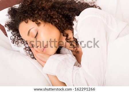 African woman sleeping in bed - stock photo
