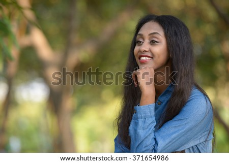 African woman smiling outdoors in park
