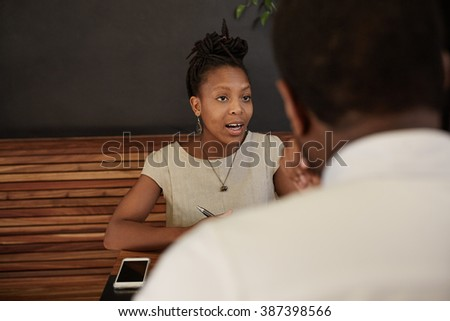 African woman talking confidently in a modern coffee shop - stock photo