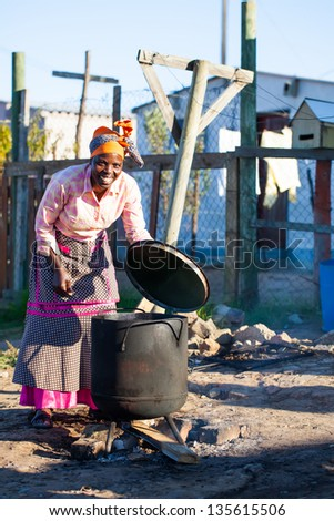 african woman watching over her dinner in big black pot outside on fire - stock photo