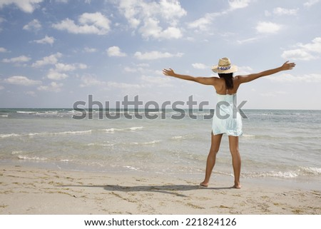 African woman with arms outstretched at beach - stock photo
