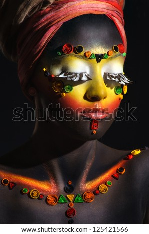 African woman with artistic ethnic makeup on her face and shoulders