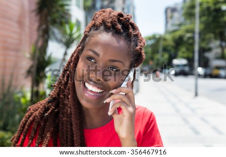 African woman with dreadlocks laughing at phone in the city - stock photo