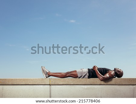 African young man lying on a wall by walkway outdoors with copy space. Muscular young fitness model relaxing after his workout against sky. - stock photo