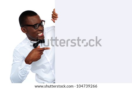 African young man pointing and looking at blank billboard wearing glasses - stock photo