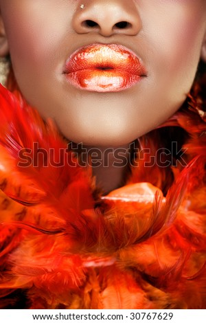 african young woman with orange feathers and orange full lips - stock photo