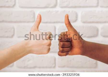 Afro American and caucasian male hands showing Ok sign,  against white brick wall, close up - stock photo