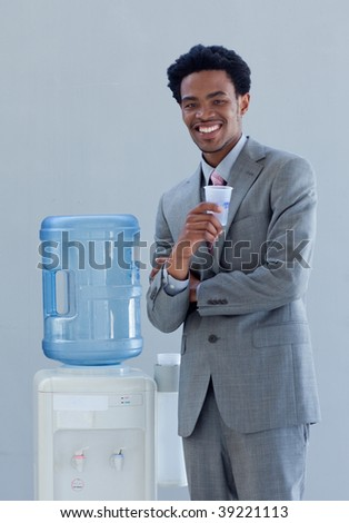 Afro-American businessman drinking from a water cooler in office