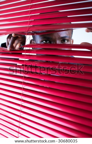 afro-american businessman glancing through red blinds. Copy space - stock photo