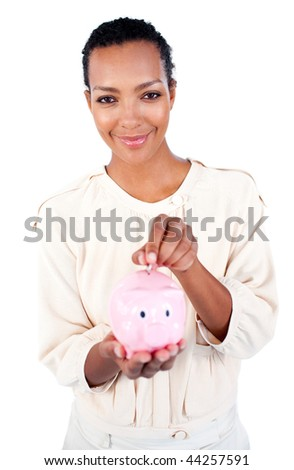 Afro-american businesswoman saving money in a piggybank against a white background
