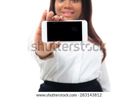 Afro american businesswoman showing blank smartphone screen isolated on a white background. Focus on smartphone - stock photo