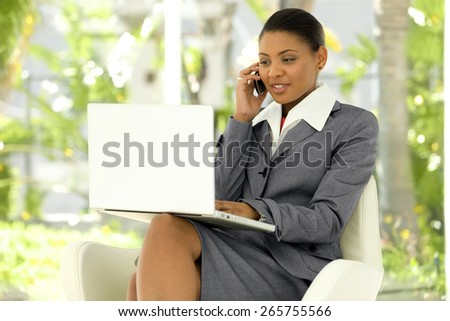 Afro American Businesswoman using laptop on knees and giving a call with smart phone - stock photo