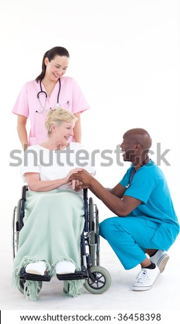 Afro-American doctor speaking to a senior patient in a wheel chair - stock photo