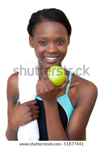 Afro-american fitness woman eating an apple against a white background - stock photo