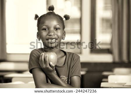 Afro american girl at elementary school holding a green apple. - stock photo