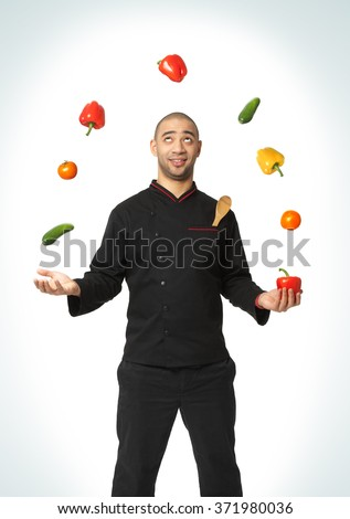 Afro American professional cook juggling vegetables - isolated on white background. - stock photo