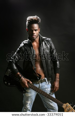 Afro american rock star musician with leather jacket and bass guitar - stock photo