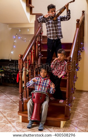 Afro children play three instruments. Three kids playing Christmas music. Christmas music tour. Come and see the talent. - stock photo