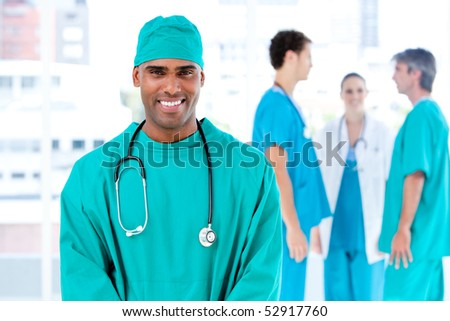 Afro male doctor looking at the camera while his medical partners talking together in the hospital - stock photo