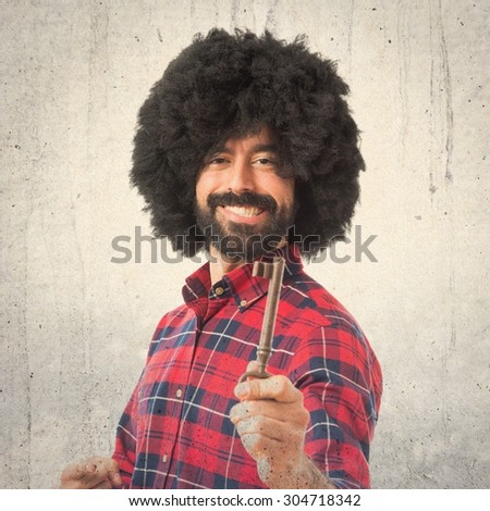 Afro man holding vintage key over textured background - stock photo